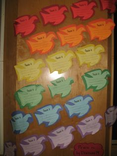 "A Rainbow of ""Peace is . . ."" writing on doves for Remembrance Day."