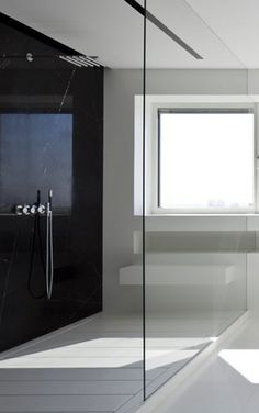Black and white bathroom with a large glass divider, apartment in Manhattan  by Pitsou Kedem