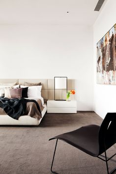 In the main bedroom, a 'Cuoio' lounge chair by Eoos for Walter Knoll and an artwork by Luke Sciberras.