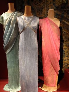 (Left to right) Scarf 1920-1940s.  Sky blue silk gauze.  Mark Walsh Leslie Chin collection.  Delphos dress 1920-1930s.  Aquamarine silk satin, silk cord, glass beads.  Regina Drucker collection.  (Middle) Delphos dress 1930s.  Ice blue silk, silk cord, glass beads.  Keith H.McCoy collection.  (Right)  Scarf 1920-1940s.  Rose print silk gauze.  Mark Walsh Leslie Chin collection. Delphos dress 1930.  Chanpagne silk.  Mark Walsh Leslie Chin collection.