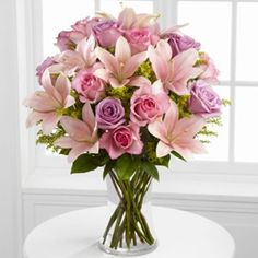 The FTD® Farewell Too Soon™ Bouquet is a blushingly beautiful way to convey your deepest sympathies for their loss. Pink and lavender roses are offset by pink Asiatic lilies, solidago and lush greens,