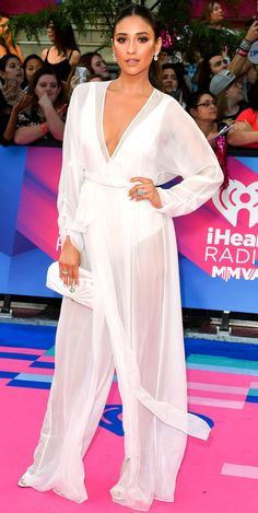 SHAY MITCHELL wears a plunging sheer August Getty Atelier jumpsuit over a white Flynn Skye bodysuit, a matching white clutch, diamond drop earrings and two statement diamond rings to the iHeartRADIO MuchMusic Video Awards in Toronto.