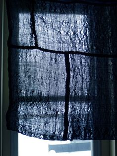 this wonderful, piece constructed sheer cotton indigo dyed koshimaki–a kind of woman's undergarment–against the silvery winter light.  The piecing and the translucency of the koshimaki is shown off to good advantage when back lit.