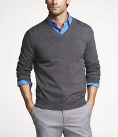 V-neck sweater over button down. Sweater sleeves pushed up revealing a hint of shirt sleeves.