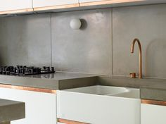 Concrete splash-back with matching worktop to create a raw, industrial look.