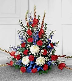 This striking arrangement is a beautiful study in contrasts, setting fiery red against pristine white and bold blues. Beautifully accented with assorted greenery and a blue satin bow. Includes carnations, chrysanthemums, delphinium, gladiolus, Monte Cassino, and more.