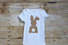 This adorable short sleeve onesie features a glitter vinyl bunny in the color of your choice with a cute white glitter vinyl tail.  I use Carters onesies, the sizing is as follows.  Newborn: Up to 21.5 inches, 5 - 8 lbs 3 Month: 21.5 - 24 inches, 8 - 12.5 lbs 6 Month: 24 - 26.5 inches, 12.5 - 16.5 lbs 9 Month: 26.5 - 28.5 inches, 16.5 - 20.5 lbs 12 Month: 28.5 - 30.5 inches, 20.5 - 24.5 lbs  Can do custom requests, if you want this with different colors send me a message and I can make…