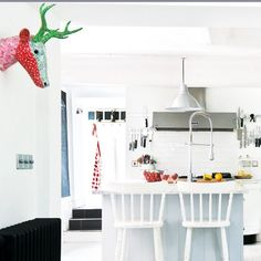 This white on white decorating idea keeps this kitchen looking bright, clean and fresh. The rest of the scheme is accessorised with quirky pieces and colour to avoid creating an overwhelming, sterile look.