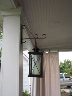 i love the white curtain for shade, and the hanging lanterns and white posts