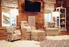 Rustic nursery design with TV, gray Moorish tiles fabric roman shades, Surya Jill Rosenwald Fallon Rug - Gray, white bookcase, Stray Dog Designs Aly Sr Floor Lamps in White, ikea rens pelts and beige tufted glider with ottoman.