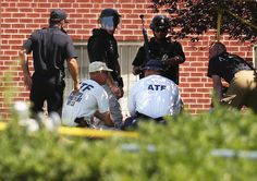 Federal, state and local law enforcement agents and explosives experts huddle after a controled detonation inside James Holmes' apartment July 21, 2012 in Aurora, Colorado.