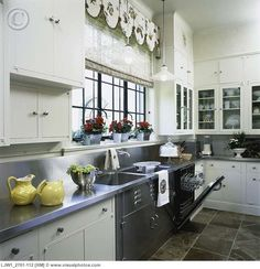 KITCHEN: Looking stainless steel dishwasher, stainless steel countertops and backsplash, window with blooming red geraniums, bamboo blind ,botanical print valance, white painted cabinets, slate floor, pendant light , industrial traditioanl [LJW1_2761-112]