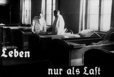 """This photo originates from a film produced by the Reich Propaganda Ministry. It shows two doctors in a ward in an unidentified asylum. The existence of the patients in the ward is described as """"life only as a burden.""""  Such propaganda images were intended to develop public sympathy for the Eutanasia Program.  --US Holocaust Memorial Museum"""