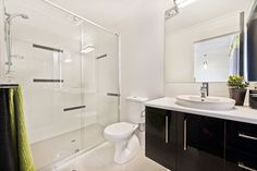 #Bathroom #ideas from Ausbuild's Segal display #home. This #Bathroom presents a clear, chic look, with a glass #shower #door and fresh white #walls. The black cupboards act as feature in this stunning bathroom. www.ausbuild.com.au
