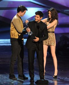 LOL Taylor accepting the award and Rob and Kristen playing behind him. LOL