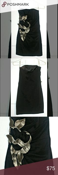 Cach? black mini dress This little black dress is in excellent condition and has flower detailing across its front side. It fits like a glove and is very short. It is 60% polyester, 32% nylon, and 8% spandex. Cache Dresses Strapless