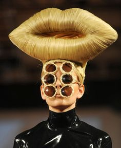 """""""British Chic in Vienna."""" From the 2010 exhibition """"Fish and Chips, Twice Please?"""", this extraordinary hair creation is by the London-based Frenchman Charles le Mindu.  [I don't know whether it's the lips or the six eyes that are making me laugh more!]"""
