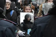 A pro-European demonstrator holds a mirror which reflects a group of riot police officer standing guard in Kiev, Ukraine