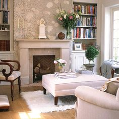This elegant room is actually a 1970s extension but reclamation yard finds like the fireplace and floorboards give it a period feel. The chimney breast is covered in floral paper to offset the pale walls and woodwork. Built-in bookcases add storage, while period and modern furniture are mixed for interest.