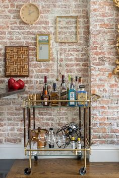 gold bar cart and gallery wall with exposed brick