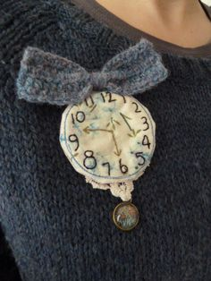 ...Mad hatter watch brooch...    ....All hand stitched and embroidered by me, by the sea from my little crafte nook...    ...Vert slightly quilted onto beautiful Cabbages and Roses fabric...    ...A crocheted bow to top it off, and a little charm stitched to some vintage trim...    Pixie xx