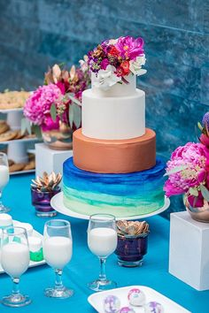 Topped with a flare of fuchsia flowers, Simply Delicious' cake formed the focal point of the dessert table. With its painterly strokes of aquatic blues, the base tier mimicked the watery work of art behind it. The four-tiered creation was flanked by goodies from Crumbs Gourmet Cookies, which stuck to clean lines and minimalist styling with its array of stark white sweets, smattered here and there with pops of color. | Photo by Ryan Green Photography