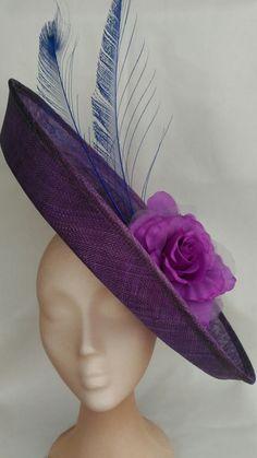 Pamela para boda morada y azul. La pamela morada ha sido combinada con una flor morada hecha a mano y plumas azul añil.  Es un sombrero para bodas