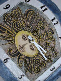 Originální+hodiny+s+tváří+slunce+Originální+keramické+hodiny+-+s+motivem+tváře+slunce.+Šířka+28+cm,+výška+24+cm,+tvář+je+reliéfní,+kvalitní+tichý+hodinový+strojek+na+tužkovou+baterii,+ručičky+bílé+kovové.+Po+okrajích+krásná+modrá+glazura+v+polomatu+v+barvě+skalní+modři+s+krémovými+efekty.+Čísla+v+bílém+poli+s+jemným+crackle+efektem.+Středová+část+...