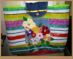 feita com material de nylom botões e flores de tecido presos em um bolso de jeans