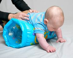Increasing Body Awareness during tummy time! Every Mom should have one of these for building awareness and stability! A great tool for helping visually impaired babies learn to crawl.