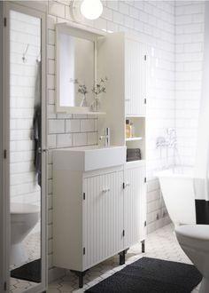 Witte badkamer met smalle wastafelkast, hoge kast en spiegelkast