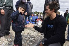 Orlando Bloom high fives with a young migrant during a visit to a refugee camp on the Mace...