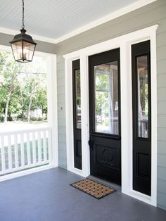 The fresh white of the trim and railing offers a pleasing contrast with the vintage front door and shutters now painted in black.