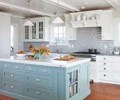 Give an all-white kitchen a lift with a refreshing coat of blue for a classic, pleasing palette with a hint of color. A cornflower-blue island and watery-hue backsplash make this white kitchen feel cheery and full of character./