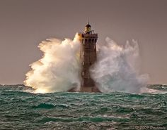 Lighthouse engulfed in waves