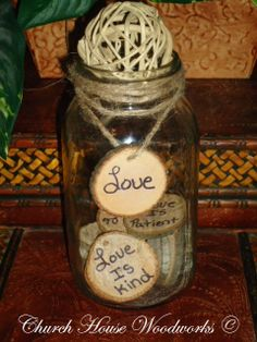Rustic decoration ideas using wood slices. Fill a jar with wood slices that have words written on them. Add some twisted Jute Twine to the top of jar. Thread a wood slice with a written word on it and tie around glass jar. Use in a rustic setting.