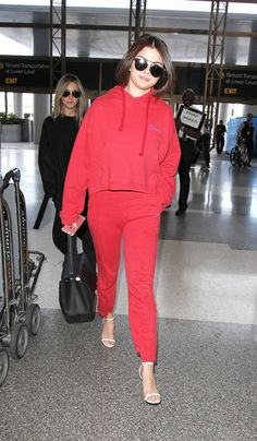 On Selena Gomez: Dior So Real Sunglasses ($620); Louis Vuitton Trocadero Bag ($2880); Vetements sweatshirt and Cut-Out Cuffs Track Pants ($665); Jimmy Choo Minny Leather Sandals ($750).