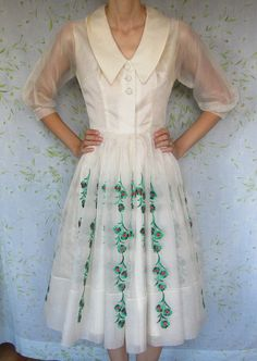 "A 1950s silk organza dress with a full embroidered skirt in red and green. The dress has a large collar, three buttons in the front, a hook and eye closure at the waist, and sheer sleeves. The maker of the dress is ""Young Modes by Claudia Young."""
