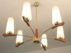 This wonderful Danish Mid-Century Modernist chandelier was designed by Stilnovo. It features a sculptural design in brass with wood detailing and has teak opaline glass shades. Mid Century Modern Chandelier, Mid Century Modern Lighting, Ceiling Lamp, Ceiling Lights, Chandelier Pendant Lights, Chandeliers, Retro Lamp, Mid Century Decor, Vintage Lamps