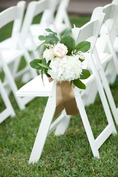 White ceremony chairs and gold ribbon tied on floral arrangements for pew markers