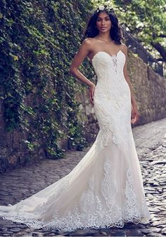 Beaded lace motifs cascade over tulle in this fit-and-flare wedding dress, accenting the illusion plunging-sweetheart neckline and illusion scoop back. Lined with shapewear for a figure-flattering fit. Finished with covered buttons over zipper closure.
