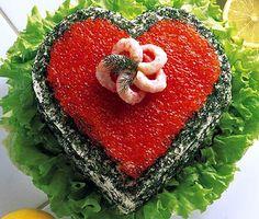 Varför inte bjuda på en vacker hjärtetårta med räkor på din kärestas födelsedag? Bred ut den krämiga skaldjursröran mellan bottnarna och dekorera sedan din goda smörgåstårta med salta räkor, rom, krispig lök och dill. Servera med citron och sallad.