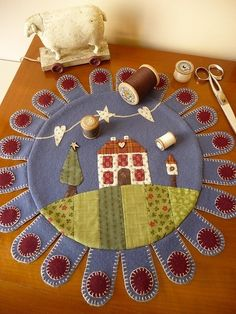 love the combination of cotton appliqued onto a wool penny rug by brittney