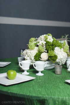 Table 12 featured a large arrangement of white hydrangeas, white roses, mini green hydrangeas, and greenery. Various frosted and white votives were placed around the table. Smaller arrangements feature green grapes in a milk glass bowl and milk glass cream and sugar bowls. The table was covered with a green table linen that had a white ruffled edge borrowed from Table Covers and More. The NotWedding was held at the W Hotel in Buckhead. Photo credit: Katey Penton Photography