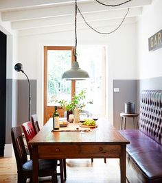 A Global Vintage Wonderland: The Vintage House Daylesford || The dining area with a Chesterfield banquette booth and a 1700s post office table from England