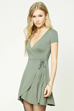 A knit dress featuring a mock wrap front with self-ties, a surplice neckline, short sleeves, and a tulip hem.