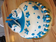 A cake made for a christening / baptising party. Covered in marzipan. the decorations and the baby converse shoes are made out of sugarpaste and gumpaste.