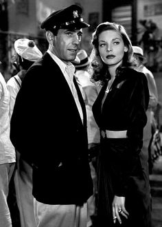 Lauren Bacall holding her own again Hollywood icon and husband, Humphrey Bogart. She looks striking in this belted black dress. #modcloth #styleicon