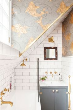 choosing metallic fixtures and fittings for this small bathroom was definitely the right thing to do to bring out the golds in the wallpaper - very luxurious