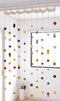 hanging pom poms threaded on yarn - great party backdrop
